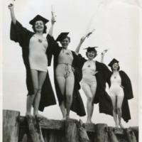 Фотография четырех веселых девушек в академических мантиях и шапочках поверх купальников