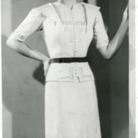 """Фотография модели в белом полотняном послеполуденном платье с гранатовым поясом """"Promenada"""" (""""Прогулка"""") от Поля Руа."""