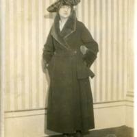 Фотография модели в пальто цвета морской волны с отделкой из бобра от от  Жозефа Пакена и шляпкой от Мари.