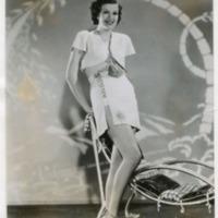 Фотография модели в пляжном костюме возле шезлонга.