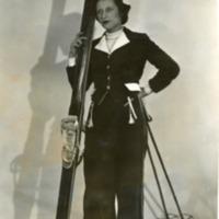Фотография модели в темном костюме с лыжами и лыжными палками