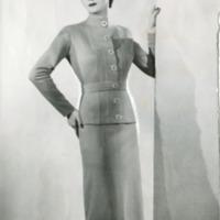 Фотография модели в светлом костюме со следами ретуши.
