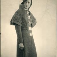 Фотография модели в серо-дымчатом ворсистом пальто с металлическими пуговицами от Брюйе.