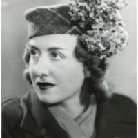 Фотография модели в темной шапочке с букетом.