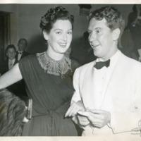 Фотография дамы в темном платье с мехами и бриллиантовыми подвесками и джентльмена в белых фраке и смокинге при темном галстуке-бабочке  во время торжественного приема.