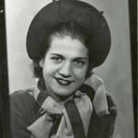 Фотография модели в темных шляпке в свитере и полосатом шарфе.