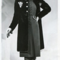 Фотография модели в черном пальто, темном платье, туфлях и шляпке.