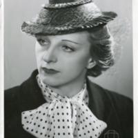 Фотография модели в черном канотье с вуалью, украшенным голубыми, красными и желтыми лентами, от Энли Сойерса