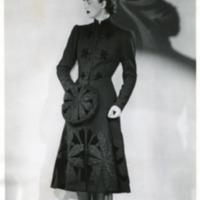 Фотография модели в черном пальто от Менделя из овечьей шерсти, расшитом цветами из каракуля и бархата, туфлях и шляпке