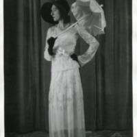 Фотография модели в белом платье с длинными рукавами от Молине (Molineyx), черных шляпке, перчатках и туфлях и с белым зонтиком.