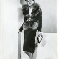 Фотография модели в темных платье с меховым подбоем, шляпке и туфлях, при темной сумочке и белых перчатках от Жана Дессе (Jean Dessès)